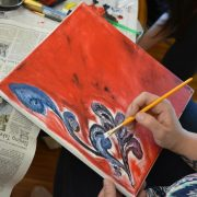 A painter covers a canvas with red paint and a blue flower.